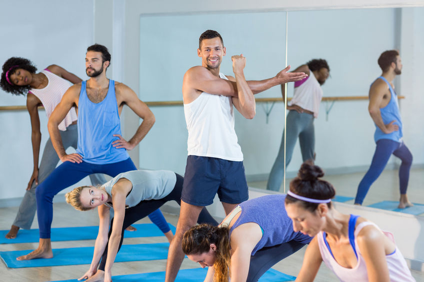 64289635 - group of people performing stretching exercise in gym